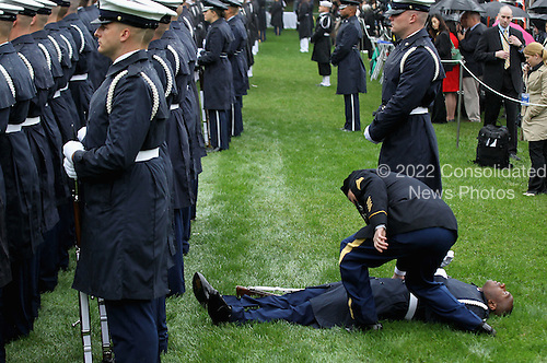 A member of the United States Coast Guard falls backwards during a welcome ceremony for President Lee Myung-bak of the Republic of Korea on the South Lawn of the White House, Thursday, October 13, 2011 in Washington, DC. Later in the day Lee is scheduled to hold a joint press conference with Obama and also address a joint meeting of Congress. .Credit: Alex Wong / Pool via CNP