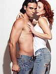 Expressive portrait of a sexy young man with bare torso wearing jeans embracing a young red haired woman in tank top. Isolated on white background.