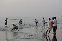 Beach fishermen pulling in Gill net through surf, Goa, Arabian sea, India