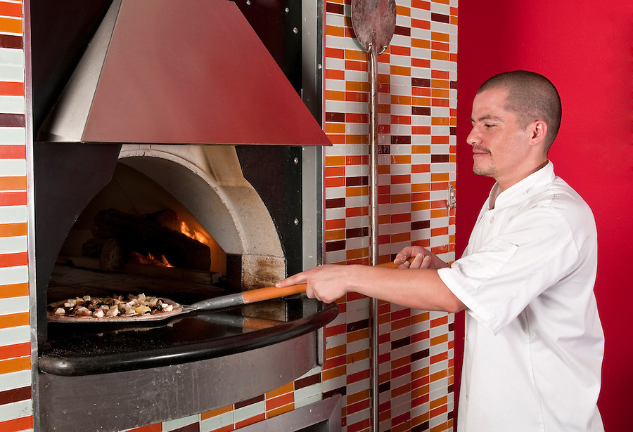 Young hispanic immigrant cooking pizza in a restaurant.