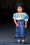 Young Guatemalan girl in traditional dress stands in a church doorway in Antigua, Guatemala