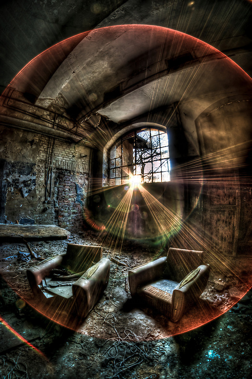 Abandoned lunatic asylum north of Berlin, Germany. Sunlight shining into empty room with two lounge chairs