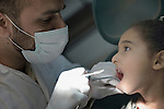 Nour Abu Hamad, 6, gets her teeth worked on by a dentist in a clinic in Darraj, a neighborhood of Gaza City that was hard hit by the Israeli military during the 2014 war. The clinic is run by the Department of Service for Palestinian Refugees of the Near East Council of Churches, a member of the ACT Alliance, and funded in part by the Pontifical Mission for Palestine.<br /> <br /> Parental consent obtained.