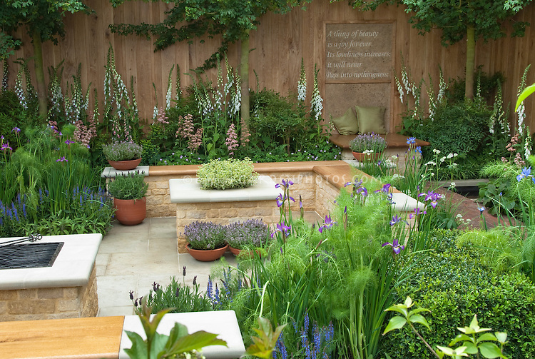 Beautiful herb patio garden: Keats A thing of beauty is a joy forever motto on garden fence wall, with bench, cushions, place to relax, foxglove white flowers, tree, privacy in backyard