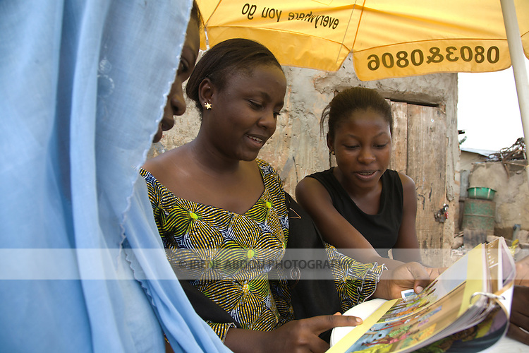 Two female out-of-school youth in the Garki area of Abuja, Nigeria look at a peer educator manual on HIV/AIDS with the Society for Family Health's Behavior Change Communication Officer.  The Society for Family Health is Nigeria's largest indigenous NGO and is affiliated with the American NGO, Population Services International.