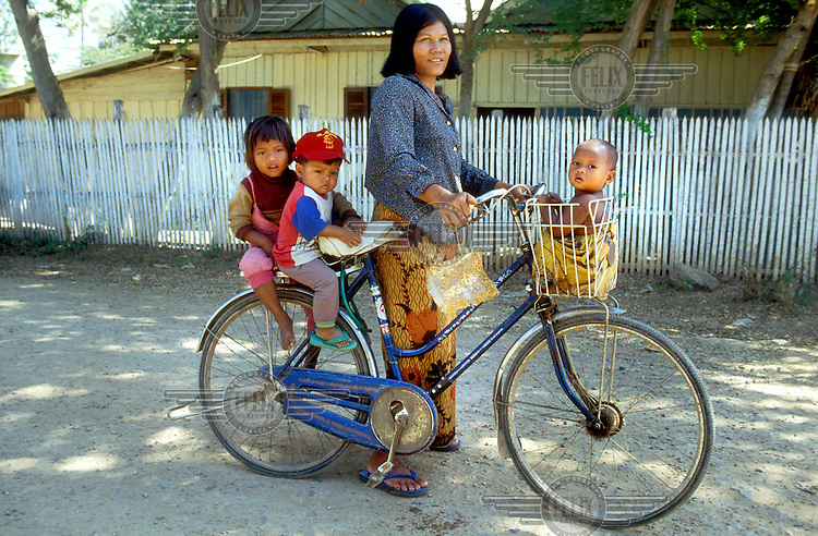 Peasant woman with three kids on her bicycle.