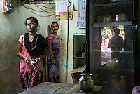 A  customer walks out of Lavanya Gattu's kitchen as she looks on in her food stall in Peddapur, a remote village in Warangal, Telangana, India, on 22nd March 2015. Lavanya buys iJal water and uses it for all her family consumption, and also cooks with it in her stall and serves it for free to customers who come to eat there. She leaves the iJal water cans at the door, showing off to her customers that she uses safe water. Photo by Suzanne Lee/Panos Pictures for Safe Water Network