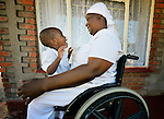 Jennifer Mhlanga suffered a spinal injury in a bus accident, and today uses a wheelchair to get around Harare, Zimbabwe. Here she sits on the porch of her house playing with her three-year old granddaughter, Tariro Bvumakurehwa. Mhlanga's wheelchair, which was carefully fitted to her individual needs, was provided by the Jairos Jiri Association with support from CBM-US.