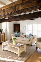The New England inspired colour scheme is in airy contrast to the massive old beams supporting the ceiling of the living room of the converted Victorian structure