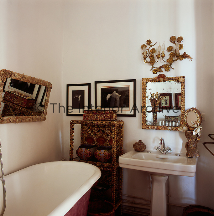A corner of a traditional bathroom with a free-standing roll top bath and a Victorian style pedestal washbasin. A small shelving unit and two mirrors are encrusted with shells. A gilded wall light is set above the basin.