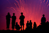 People silhouetted at night watching the Strombolian eruption of Yasur Volcano, Vanuatu.