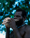 Shark caller Robert from Tembin village on the West Coast blows his conch shell..Kontu, New Ireland Province, Papua New Guinea;