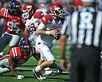 Arkansas quarterback Tyler Wilson (8) is chased by Ole Miss' Charles Sawyer (3) at Vaught-Hemingway Stadium in Oxford, Miss. on Saturday, October 22, 2011. .
