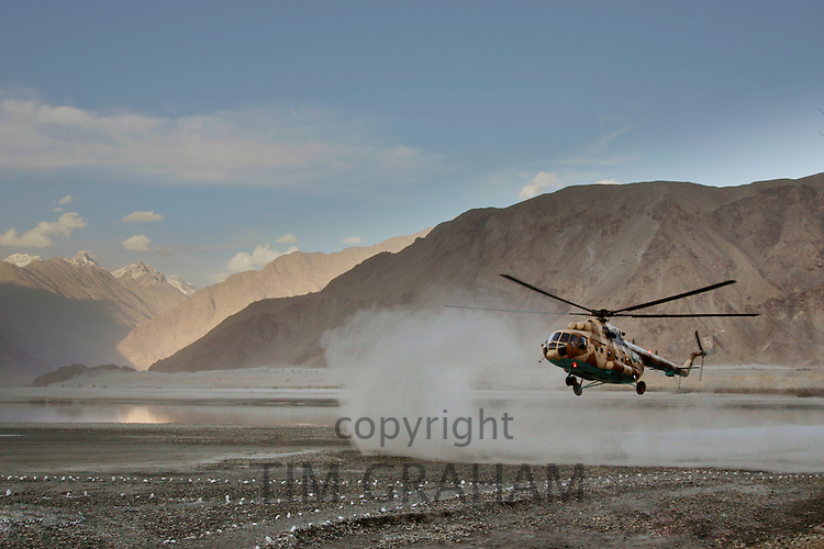 Helicopter lands on heliport in valleys of Karokoram Mountains, Skardu Valley, North Pakistan