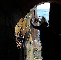 Lighthouse keeper opening the entrance door at low tide, in the Phare de Cordouan or Cordouan Lighthouse, built 1584-1611 in Renaissance style by Louis de Foix, 1530-1604, French architect, located 7km at sea, near the mouth of the Gironde estuary, Aquitaine, France. This is the oldest lighthouse in France. There are 4 storeys, with keeper apartments and an entrance hall, King's apartments, chapel, secondary lantern and the lantern at the top at 68m. Parabolic lamps and lenses were added in the 18th and 19th centuries. The lighthouse is listed as a historic monument. Picture by Manuel Cohen