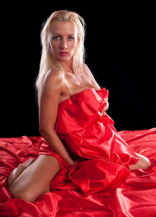 30 something caucasian woman very sexy and naked covered with red silk sheet.