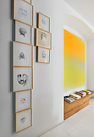 A collection of illustrations is displayed on a wall. Beside it hangs a vibrant yellow artwork in a slight alcove, where books are arranged on a wooden bench seat below.