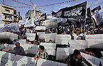 Palestinian supporters of Hizb ut-Tahrir wave black and white flags as they take part in a rally marking the anniversary of the fall of the Islamic Caliphate, in the West Bank city of Ramallah May 31, 2014. Photo by Issam Rimawi