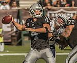 Oakland Raiders quarterback Derek Carr (4) looks for receiver on Sunday, October 9, 2016, at O.co Coliseum in Oakland, California.  The Raiders defeated the Chargers 34-31.