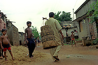 The village of Padmakesharpur in the state of Orissa in East India is probably the largest community of snake charmers anywhere in the world. 200 charmers live in the village, but each year they find it harder to make a living from charming and their numbers are slowly diminshing. Having been out charming for several weeks a charmer returns to the village carrying his snakes in the baskets.