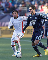 Sporting Kansas City midfielder Soony Saad (22) dribbles as New England Revolution midfielder Lee Nguyen (24) closes.  In a Major League Soccer (MLS) match, Sporting Kansas City (blue) tied the New England Revolution (white), 0-0, at Gillette Stadium on March 23, 2013.