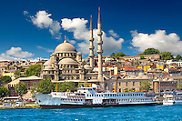The Yeni Camii, The New Mosque or Mosque of the Valide Sultan ordered by Safiye Sultan in 1597 with a ferry on  the banks of the Golden Horn, Istanbul Turkey.