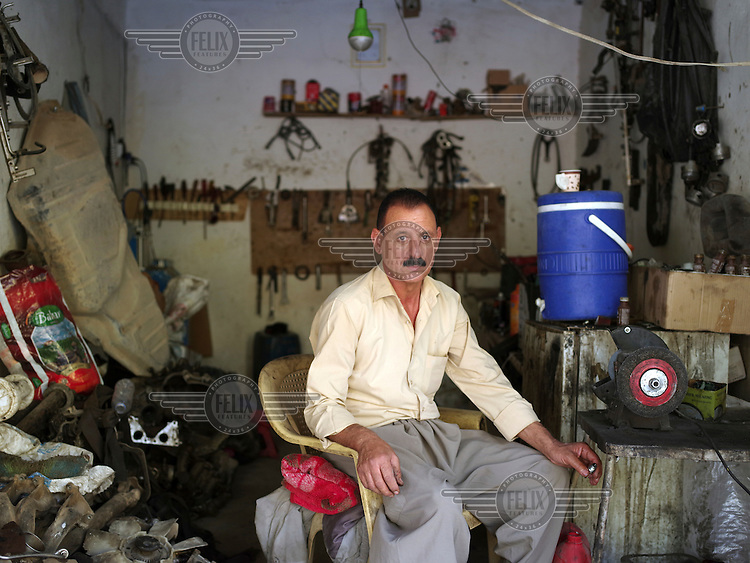 Qasim in his mechanic's workshop in the Sharia district near Dohuk. 'When ISIS attacked my village in Sinjar, on 3 August 2014, I ran away with my family. One month before ISIS attacked my village, I sold my Toyota car. With this money, I was able to open this mechanic's workshop only seven days after I evacuated to Sharia in August 2014. I had my own shops in Sunni and Zorava villages in Sinjar.'