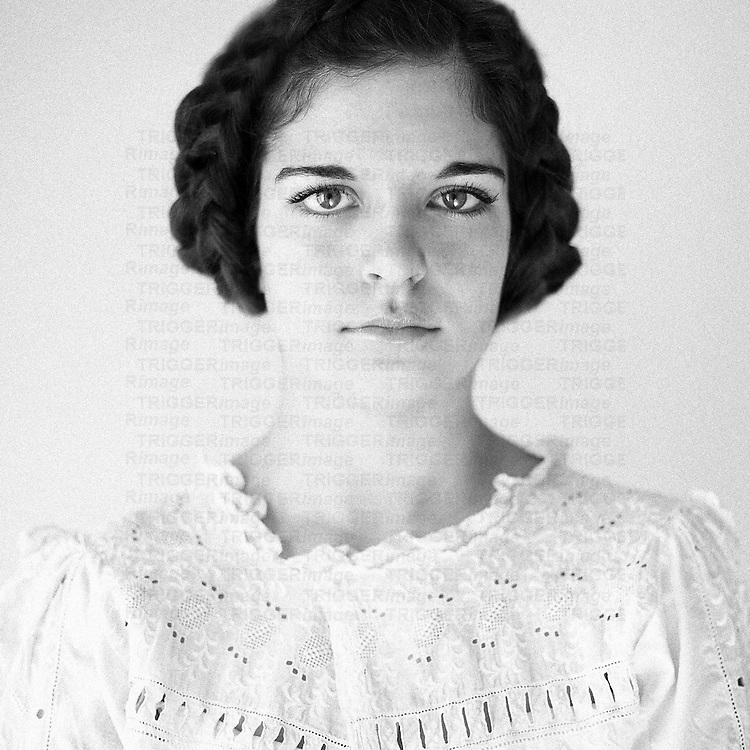 Close up of young woman with dark hair wearing white lace dress looking at camera