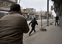 Men run down a thoroughfare in the Arbin suburb of Damascus as a sniper fires down the street, the district has come under sustained attack during a government attempt to restore its control over the area. Protests against the ruling Baathist regime erupted in March 2011and although they were peacefully government forces violently repressed them. In response to being commanded to shoot unarmed civilians large numbers of men deserted the army and formed the Free Syrian Army and an armed uprising began with major clashes taking place in early 2012..
