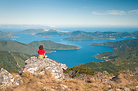 A hiker admires stunning views from the highest peak in Marlborough Sounds - Mt. Stokes 1203m toward the Endeavour Inlet and further toward the North Island - Marlborough, New Zealand