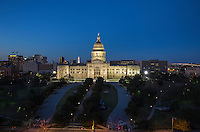 Nighttime shot of the floodlit Texas State Capitol Building with UT Tower and Wells Fargo Bank Tower in the background, Austin, Texas.