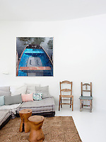 Large square cushions form a low comfortable seating area in the corner of the living room. A large photograph hangs on the wall behind