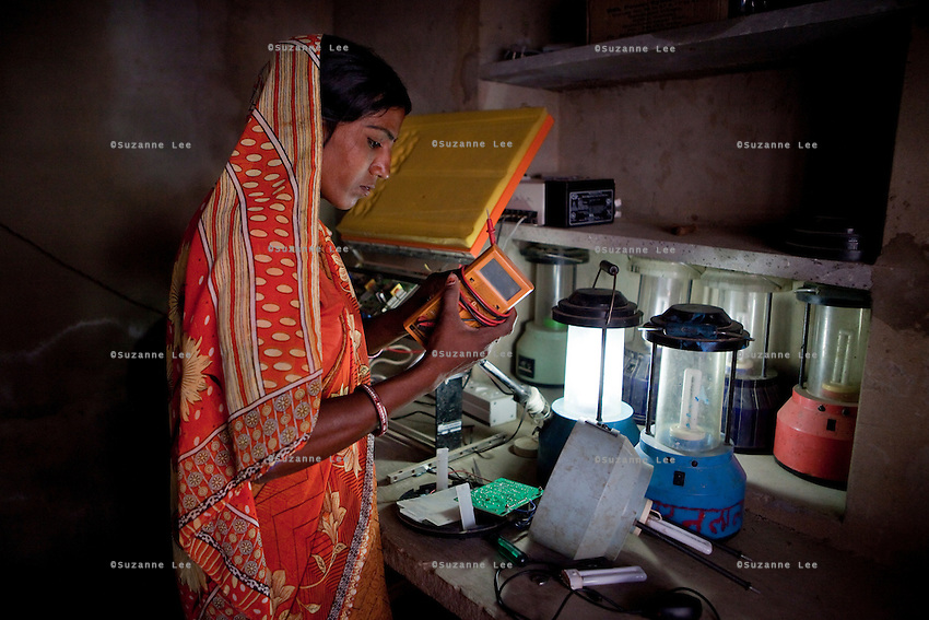 Santosh Devi, aged 19, fixes some solar lanterns in her workshop at home. She graduated 2 years ago from the solar engineering course of the Barefoot College in Tilonia, Ajmer, Rajasthan, India. She has since solar powered 20 homes in her village, Balaji Ki Dhani, Bauli, Nagur District, Rajasthan, making it the first village in India to be 100% solar powered in all houses. Above this, she does all maintenance for the neighbouring village, Gudda Ki Dhani, where the previous male solar engineer had left the village to find unrelated work in the city. Barefoot College prefers training women to be solar engineers for this reason that they have higher chances of staying in the village instead of moving to the cities. Photo by Suzanne Lee for Panos London