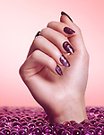 Closeup of woman's hand with purple nail polish coming out of a sea of candy