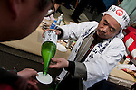 Festival workers pour alcoholic drinks (saki) called Omiki for visitors  in the grounds of Wakamiya Hachiman gu shrine during the Kanamara matsuri, Kawasaki Daishi, Japan April 5th 2009