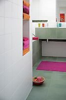 Bright orange and pink towels add a splash of bold colour to the tiled bathroom