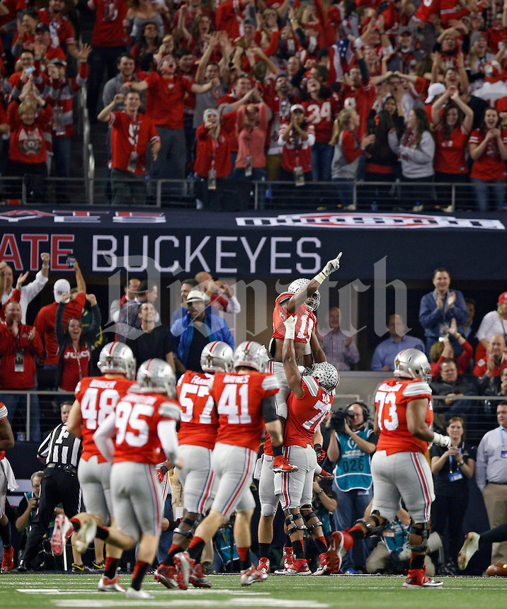 Ohio State Buckeyes offensive lineman Darryl Baldwin (76) throws Ohio State Buckeyes running back Ezekiel Elliott (15) up into the air after Elliott scored on a touchdown run against Oregon Ducks during the 1st quarter in College Football Playoff Championship game at AT&T Stadium in Arlington, Texas on January 12, 2015.  (Dispatch photo by Kyle Robertson)