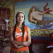 Cassinca, 18 years old married Roma girl, stands in front of a mermaid painted on the wall of a new home, in the new part of the camp. Mermaids are very popular as wall decoration, but no-one within the camp knows the reason why they were first painted..