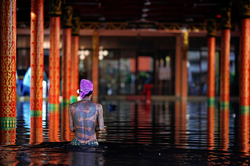 A tattooed man wades through a flooded temple where hundreds of victims found shelter in Bangkok November 1, 2011. Anger mounted among victims of Thailand's catastrophic floods on Tuesday as water flooded new neighborhoods as it made its way to sea and the government plotted a recovery aimed at securing the long-term confidence of investors.   REUTERS/Damir Sagolj (THAILAND)