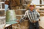 Portrait of Guatemalan man with cowboy hat in front of church bell in San Juan La Laguna, Lake Atitlan, Guatemala
