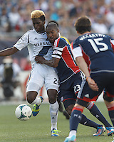 LA Galaxy forward Gyasi Zardes (29) dribbles against tenacious defender New England Revolution defender Jose Goncalves (23). In a Major League Soccer (MLS) match, the New England Revolution (blue) defeated LA Galaxy (white), 5-0, at Gillette Stadium on June 2, 2013.