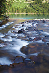 Water of east rosebud creek flowing over rocks at the inlet of rainbow lake in the beartooth wilderness of montana