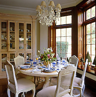 The breakfast room has a French-style wooden table and matching chairs positioned in a large bay window