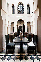 The riad's central courtyard is furnished with wooden benches and tables at either end and has a series of large ceramic urns flanking the central water feature