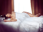 Beautiful young asian woman lying naked in bed covered with white sheets with bright light coming from the window