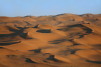 Namib Desert sand dunes in Namibia formed by the powerful force of desert winds that gradually push the dunes in a north-westerly direction.