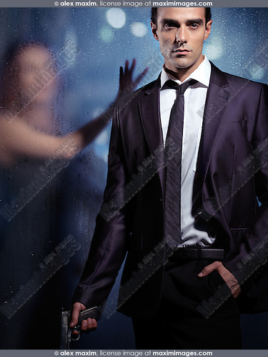 Dramatic portrait of a young woman in a suit holding a gun in his hand, and a woman standing behind a wet glass outside. Hitman, killer, assassin, revenge concept.