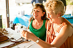 Watertown, CT- 18 May 2017-051817CM05-  Joann Basile of Plymouth, left, and Lisa Labonte of Thomaston share a laugh during the annual Greater Waterbury Campership Fund picnic at Camp Mataucha in Watertown on Thursday. The fundraiser featured a myriad of pizza options from  Big Green Pizza Truck out of New Haven, music from the Holy Cross students  with proceeds allowing children to go to summer camp.    Christopher Massa Republican-American