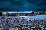 A beach at dusk with storm clouds overhead.