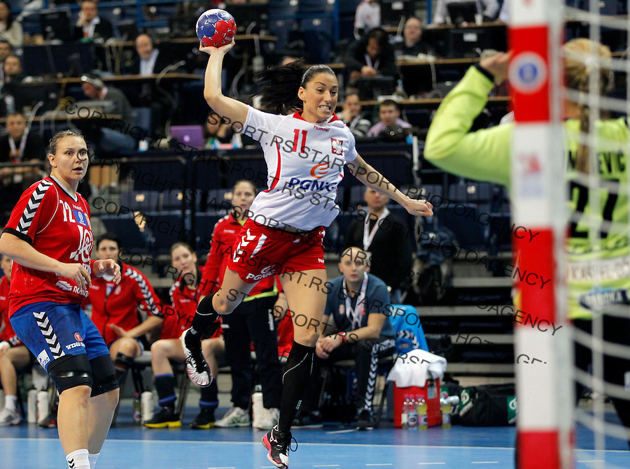 BELGRADE, SERBIA - DECEMBER 20:  Kinga Grzyb (C) of Poland jump to score near  goalkeeper Katarina Tomasevic (R) of Serbia during the World Women's Handball Championship 2013 Semi Final match between Poland and Serbia at Kombank Arena Hall on December 20, 2013 in Belgrade, Serbia. (Photo by Srdjan Stevanovic/Getty Images)